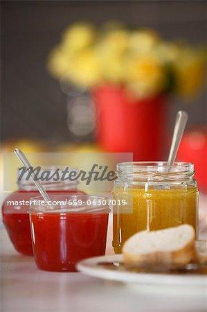 Divers pots de confiture, marmelade de fraise, poivre (orange) et chutney et pain blanc