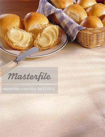 Abendessen Rollen in einem Korb; Einige auf einem Teller mit Butter
