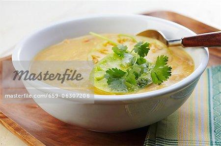Un bol de courge crémeuse et soupe de maïs aux tomatilles et garnir de coriandre