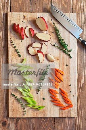 Pommes de terre rouges hachés, de carottes et de céleri au thym sur une planche à découper ; D'en haut