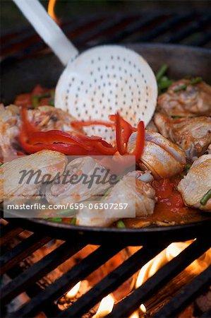 Paella dans une grande casserole sur un feu ouvert
