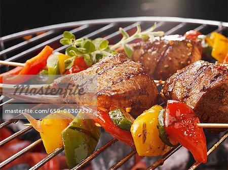 Brochettes de légumes et des côtes à un barbecue