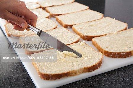 Verbreitung von Butter auf Brot in Vorbereitung auf ein Omelett-Auflauf