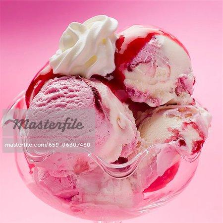Raspberry and vanilla ice cream with raspberry sauce and cream (close-up)