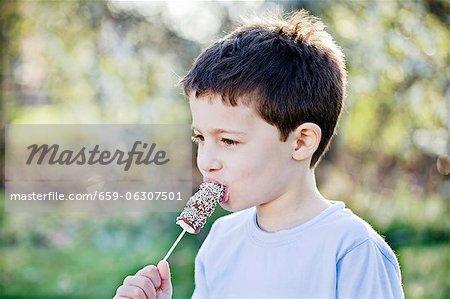 A little boy eating marshmallows