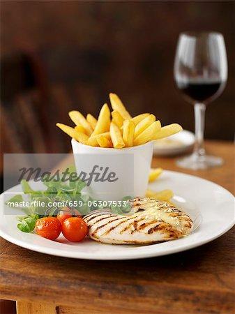 Poitrine de poulet avec l'ail, frites et un verre de vin rouge