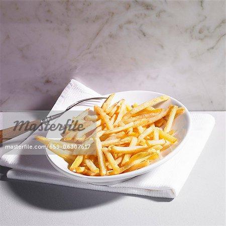 Une assiette de frites avec une fourchette