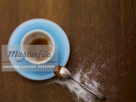 Une tasse à espresso presque vide et sucre saupoudré à côté d'elle