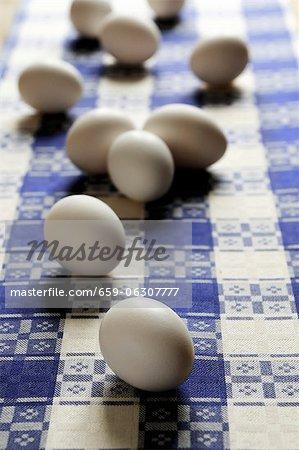 Weiße Eier auf eine geprüfte Geschirrtuch