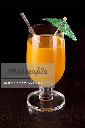Un smoothie orange avec un parapluie cocktail