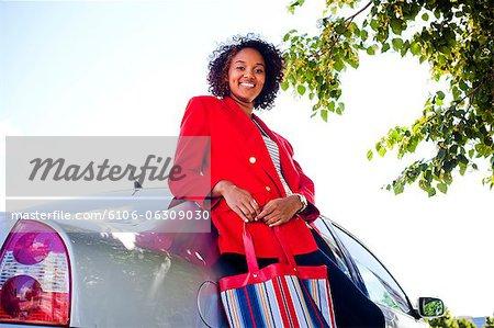 Porträt eines jungen Mädchens, das neben einem Auto steht.