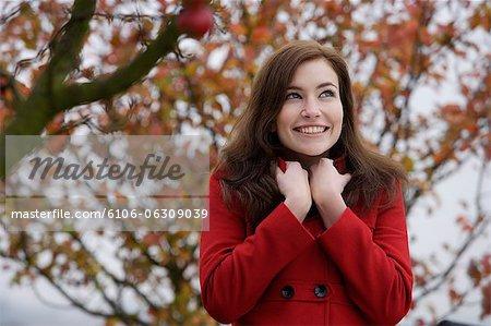 jeune femme en manteau rouge sous le pommier