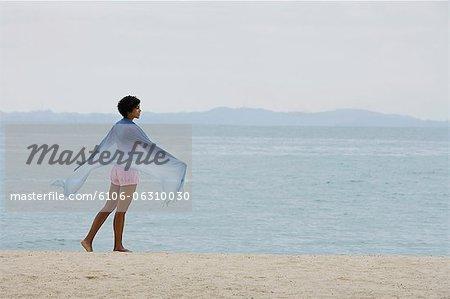 Femme foulard bleu en regardant l'océan.