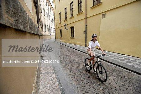 Junge Frau Fahrradfahren auf Kopfsteinpflaster-Straße