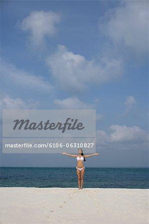 jeune femme en bikini blanc sur la plage