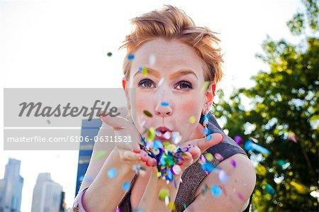 Ein junges Mädchen bläst Konfetti außerhalb.