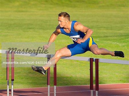 Male hurdler clearing hurdle