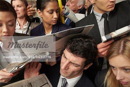 Gens d'affaires, lire des journaux sur train bondé