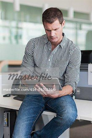 Man concentrating on digital tablet