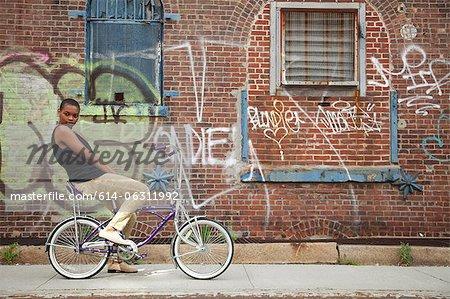 Porträt einer jungen Frau auf dem Fahrrad durch die Wand in Graffiti bedeckt