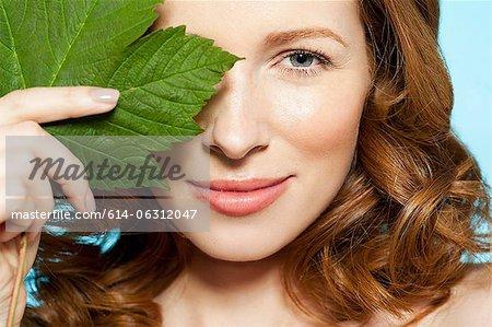 Frau Auge mit grünen Blatt abdecken