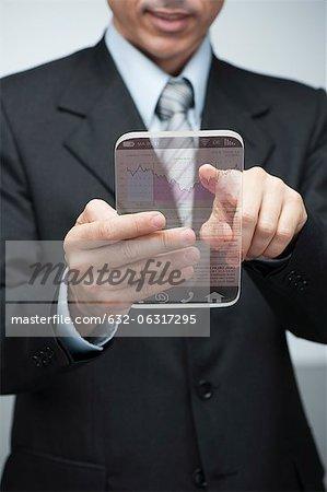 Homme d'affaires en utilisant advanced tablette numérique pour accéder aux données de marché boursier, recadrée