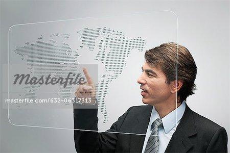 Homme d'affaires à l'aide de la technologie d'écran tactile avancé pour afficher la carte du monde