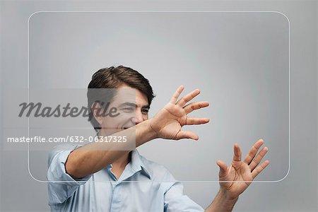 Homme avec écran large tactile transparent