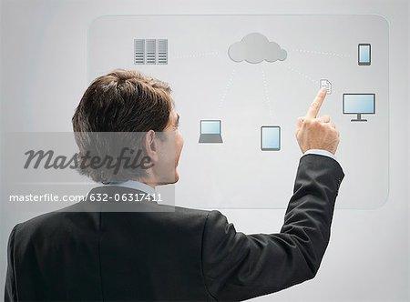 Homme d'affaires utilisant le cloud computing technologie sur un écran tactile avancé