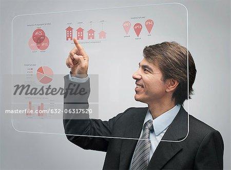 Homme d'affaires à l'aide de la technologie d'écran tactile avancé pour afficher des données sur les ventes