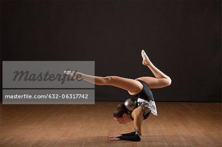 Gymnast bending backwards, balancing ball with head