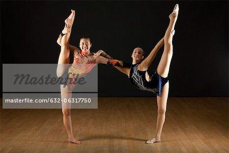 Gymnasts performing standing splits together, portrait