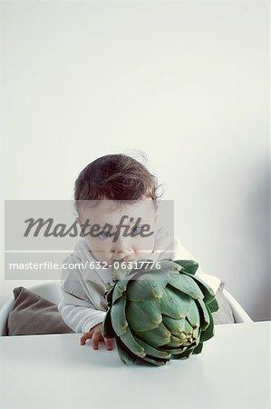 Kleinkinder beißen in Artischocken Stiel, Porträt