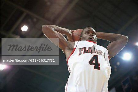 Basketball player shooting basketball, low angle view