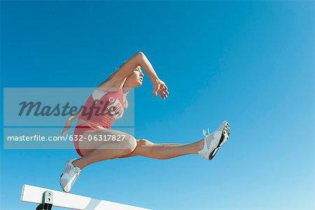 Famale Athlet springen über die Hürde, Flachwinkelansicht