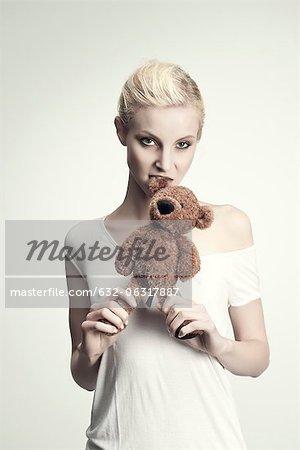Jeune femme mordant ours en peluche, portrait