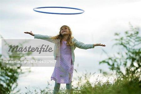 Girl throwing plastic hoop in air