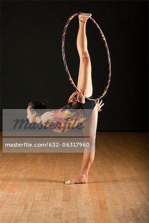 Gymnast performing standing splits with hoop