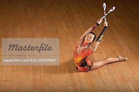 Gymnast bending backwards, holding clubs