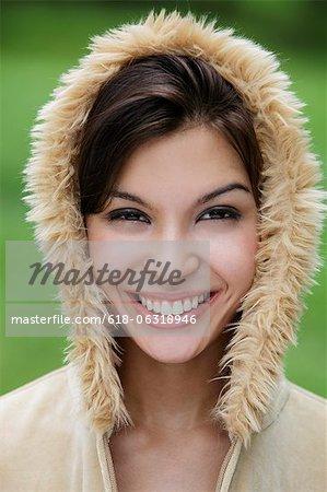 coup de tête de sourire de jeune femme portant capuche fourrure.
