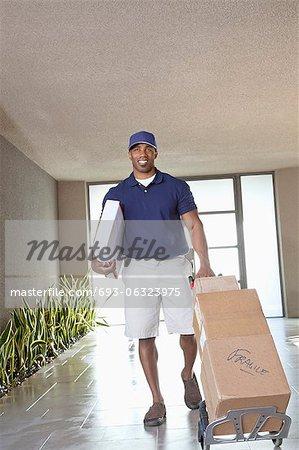 Heureux livreur afro-américain avec des paquets
