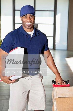 Portrait d'un homme afro-américain heureux transportant des boîtes de livraison