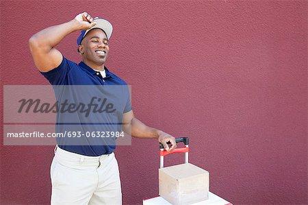 Heureux livreur afro-américains jeune debout avec le diable sur fond coloré