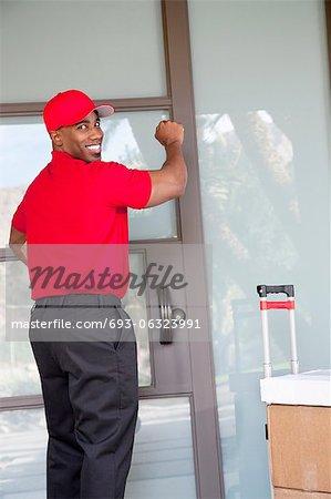 Jeune livreur avec paquets regarder en arrière tout en frappant à la porte