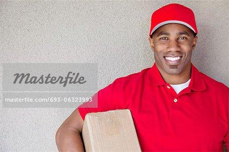 Portrait d'un homme afro-américain livraison maintenant paquet contre mur