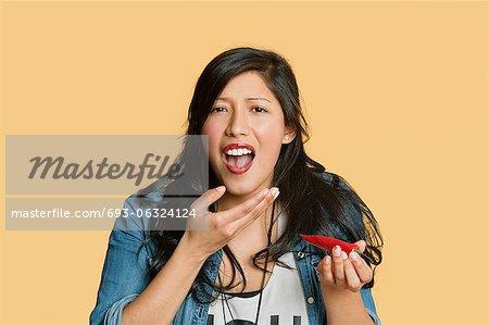 Porträt einer jungen Frau, die red hot Chili Pepper über farbigen Hintergrund Essen