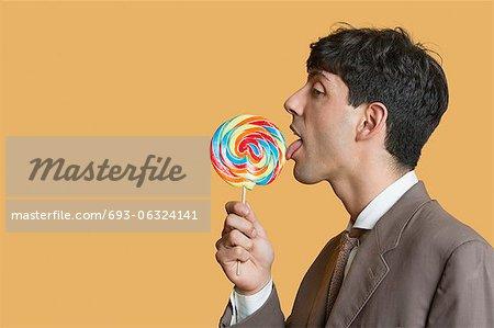 Seitenansicht des jungen Geschäftsmann lecken Lutscher über farbigen Hintergrund