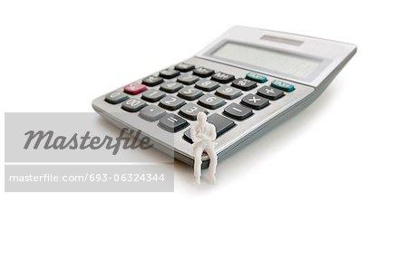 Un petit personnage mannequin assis sur une calculatrice sur fond blanc