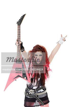 Portrait de jeune femme avec qui sort la langue et la tenue de guitare électrique sur fond blanc