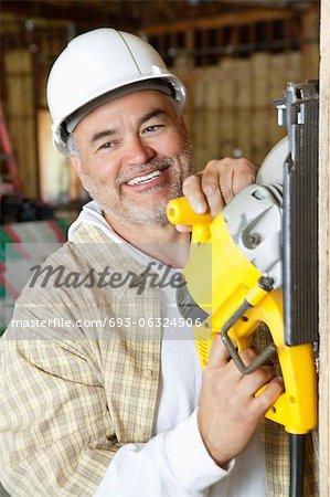 Glücklich Reife männliche Arbeitnehmer schneiden Bauholz mit einer Kreissäge